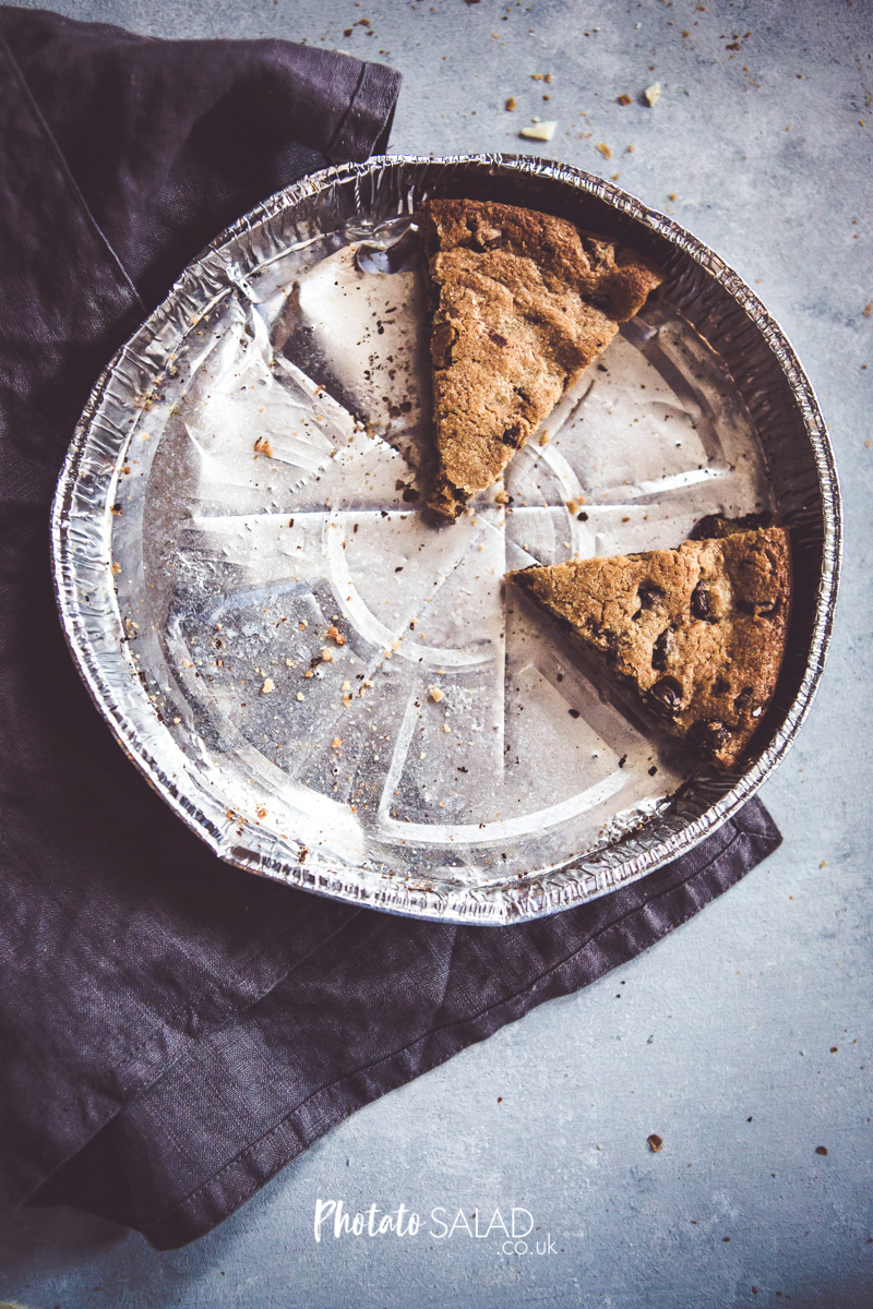 Flatlay of Rustic Cookie Slices in a tin with grey linen napkin and hand painted background