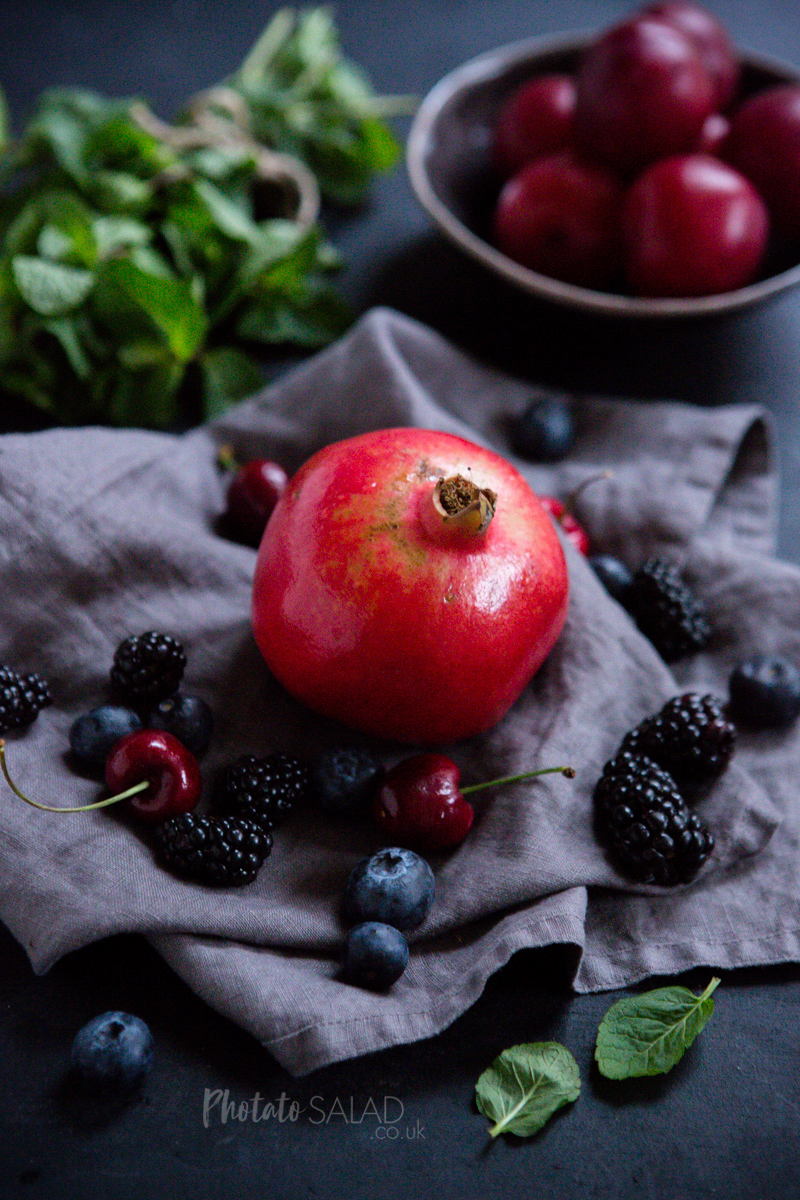 Pomegranate and Summer Berries on a grey linen napkin with fresh mint