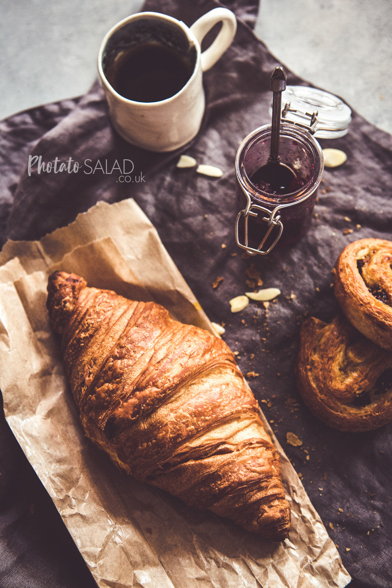 Breakfast Croissants with jam, black coffee and a linen napkin, on a grey background